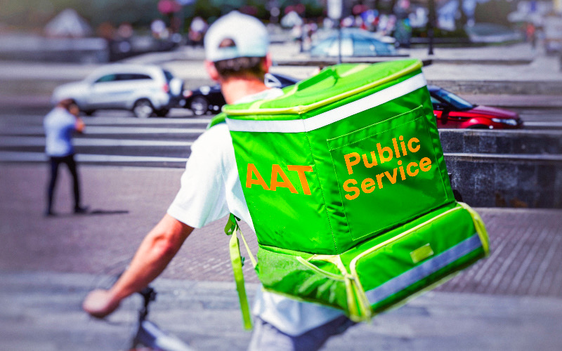 """Photo of man on bike carrying green box on his back with the words """"AAT Public Service"""""""